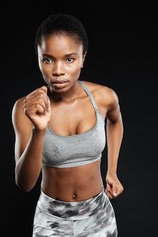 Zbliżenie portret sportowej kobiety biegającej na białym tle na czarnej ścianie