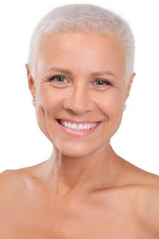 Zbliżenie portret starsza dama z zdrową skórą i jaskrawym uśmiechem odizolowywającymi na bielu