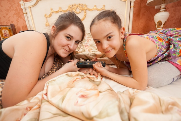 Zbliżenie portret starszej i młodszej siostry ciągnącej pilota do telewizora