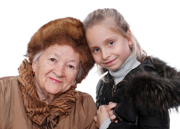 Zbliżenie portret starszej kobiety z małą wnuczką w zimie znosić