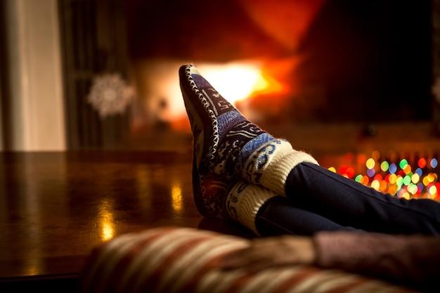 Zbliżenie portret stóp w wełnianych skarpetach ocieplających się przy kominku w zimie