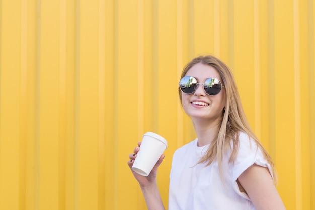 Zbliżenie portret szczęśliwa kobiety pozycja na żółtej ścianie z papierową filiżanką kawy w ona ręki i ono uśmiecha się.