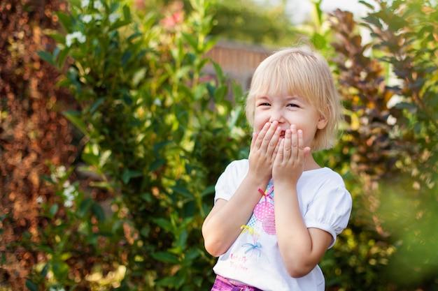 Zbliżenie portret szczęśliwa mała dziewczynka blobde w wieku szkoły podstawowej na zewnątrz w zielonym parku