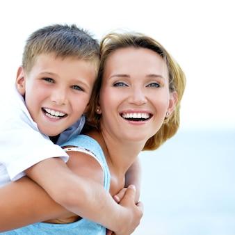 Zbliżenie portret szczęśliwa matka i syn w uścisku na plaży.