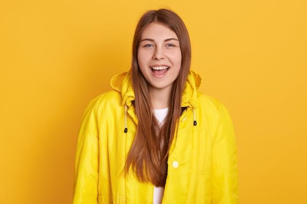 Zbliżenie portret szczęśliwa uśmiechnięta studencka dziewczyna jest ubranym kurtkę, wrzeszczy coś szczęśliwie, stać odizolowywam nad kolor żółty ścianą, wyrażający pozytywne emocje.