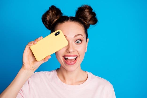Zbliżenie portret szczęśliwa wesoła dziewczyna zamykająca oko z komórką urządzenia cyfrowego