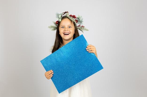 Zbliżenie portret szczęśliwej pięknej dziewczyny w bożonarodzeniowym wieńcu i białej sukni, trzymającej niebieskie błyszczące b...