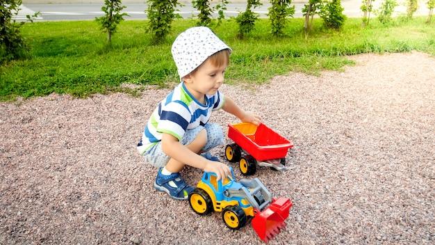 Zbliżenie portret szczęśliwy uśmiechający się 3-letni chłopiec dziecko kopiący piasek na placu zabaw z zabawkową ciężarówką z tworzywa sztucznego lub koparki