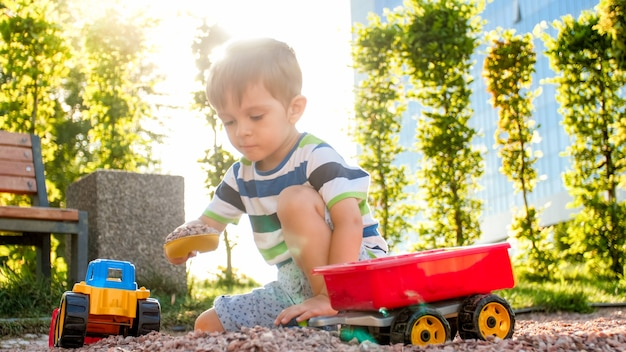 Zbliżenie portret szczęśliwy uśmiechający się chłopiec 3 lat dziecko kopanie piasku na placu zabaw z ciężarówką z tworzywa sztucznego zabawki lub koparki. dziecko bawiące się i bawiące się w parku latem