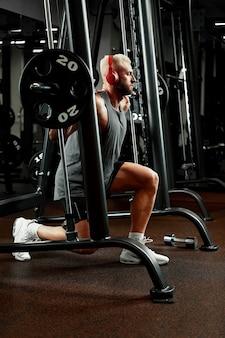 Zbliżenie portret treningu mięśni człowieka ze sztangą w siłowni. brutalny kulturysta wysportowany mężczyzna z sześciopakiem, doskonałymi mięśniami brzucha, ramionami, bicepsami, tricepsami i klatką piersiową.