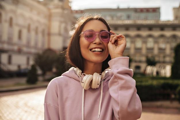 Zbliżenie portret uroczej brunetki w różowych okularach przeciwsłonecznych i bluzie z kapturem, szczerze się uśmiecha i pozuje ze słuchawkami na zewnątrz