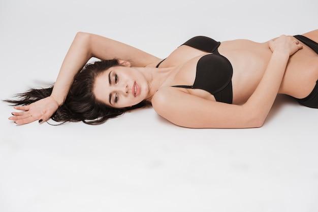 Zbliżenie portret uroczej, delikatnej kobiety w czarnej bieliźnie leżącej na plecach i odwracającej wzrok na białym tle