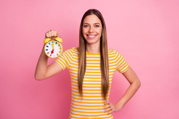Zbliżenie portret uroczej wesołej dziewczyny trzymającej w rękach zegar