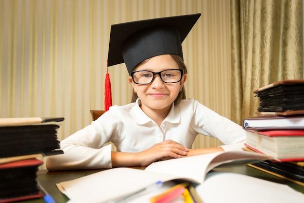 Zbliżenie portret uśmiechnięta dziewczynka w kapeluszu graduacyjnej siedzi przy stole