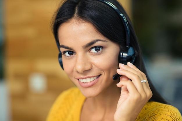 Zbliżenie portret uśmiechniętej dorywczo bizneswoman ze słuchawkami
