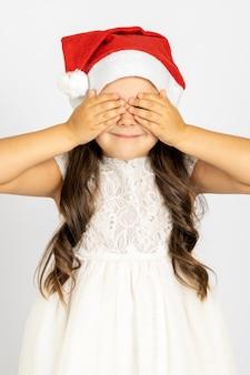 Zbliżenie portret uśmiechniętej dziewczyny z długimi lokami w białej sukni w czerwonym santa hat zakrywającym oczy ...