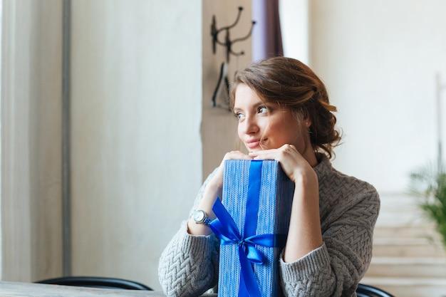Zbliżenie portret uśmiechniętej kobiety z pudełkiem, patrząc na kamerę