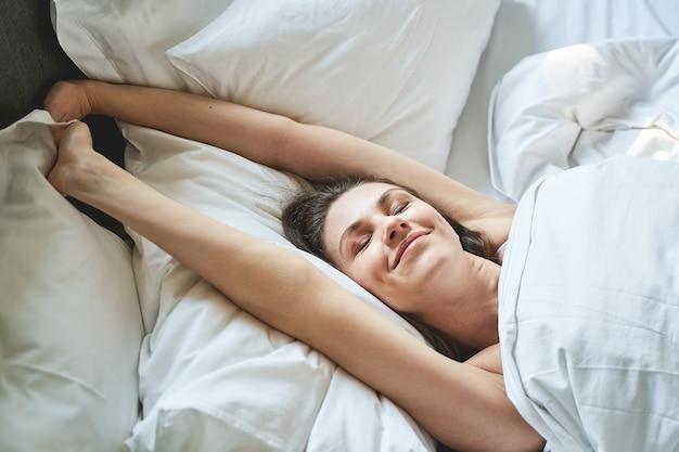 Zbliżenie portret uśmiechniętej ślicznej młodej kobiety rozciągającej się w łóżku rano