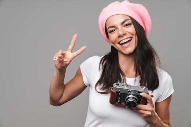 Zbliżenie portret wesołej ładnej turystycznej kobiety w berecie śmiejącej się i pokazującej znak pokoju, trzymając aparat retro na białym tle nad szarą ścianą
