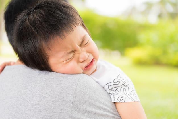 Zbliżenie portret wzburzona mała dziewczynka płacze na jej matki ramieniu.
