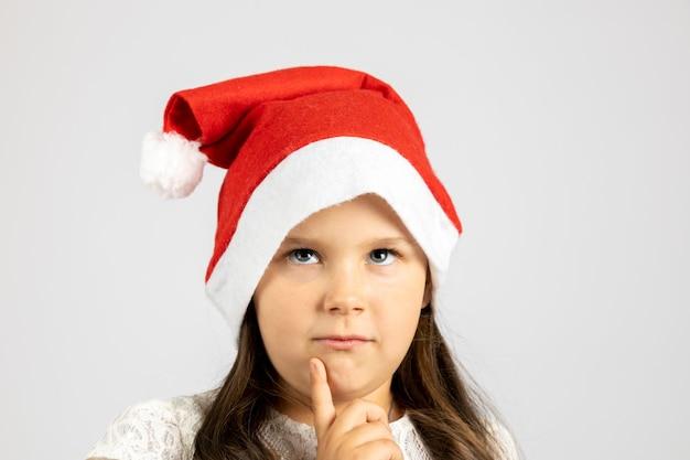 Zbliżenie portret zamyślona dziewczyna w czerwonym santa hat z palcem na twarzy na białym tle na białym tle...