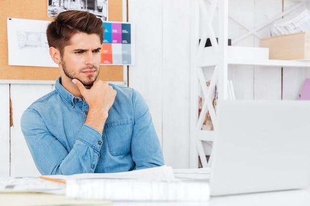 Zbliżenie portret zamyślonego młodego biznesmena dorywczo siedzącego przy biurku i korzystającego z laptopa w biurze