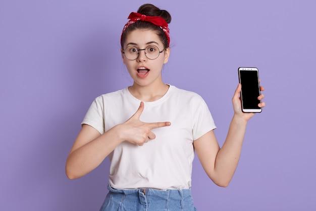 Zbliżenie portret zdumionej kobiety pozowanie z otwartymi ustami i trzymając nowoczesny inteligentny telefon z pustym ekranem