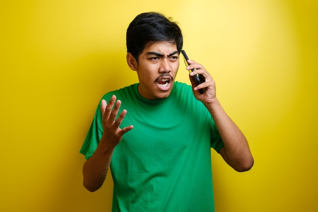 Zbliżenie portret zły młody człowiek azjatyckich, facet szalony student, wkurzony pracownik krzyczy, podczas gdy na telefon na białym tle żółtej ścianie. negatywna ludzka emocja wyraz twarzy uczucie postawa
