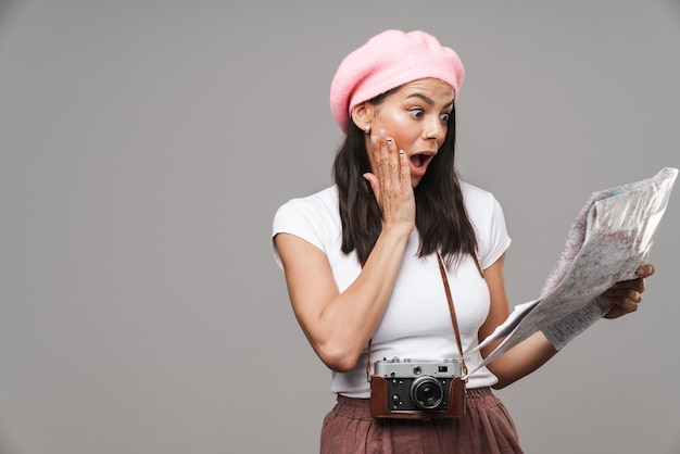 Zbliżenie portret zszokowanej młodej kobiety turystycznej z retro vintage aparatem, zastanawiającej się i trzymającej papierową mapę na białym tle nad szarą ścianą