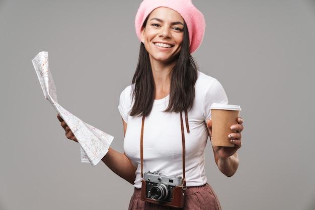 Zbliżenie portreta kaukaski młoda turystka kobieta z retro starodawny aparat i kawa na wynos uśmiechnięta i trzymająca papierową mapę na białym tle nad szarą ścianą