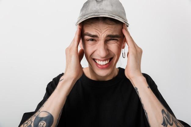 Zbliżenie portreta młodego chorego mężczyzny noszącego czarne ubrania dotykające jego skroni, mający ból głowy na białym