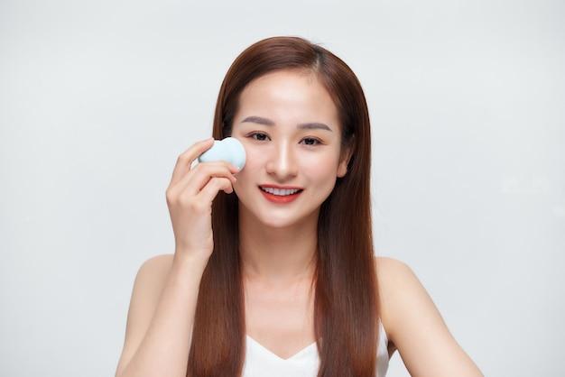 Zbliżenie portreta młodej kobiety stosującej kosmetyki za pomocą gąbek do makijażu izolowanych na białym tle
