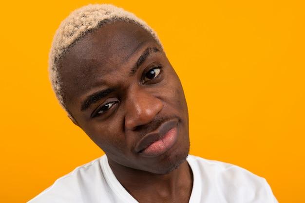 Zbliżenie portreta młody czarnego afrykanina mężczyzna w białej koszulce pozuje na kolorze żółtym odizolowywającym
