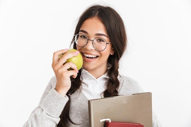 Zbliżenie portreta radosnej nastoletniej dziewczyny w okularach, uśmiechającej się i jedzącej zielone jabłko, trzymając jednocześnie studiując książki izolowane nad białą ścianą