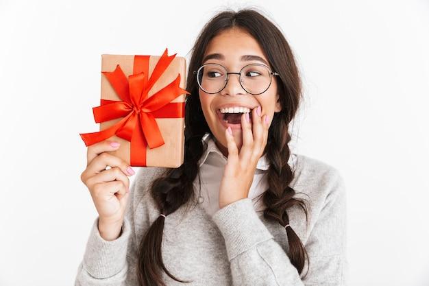 Zbliżenie portreta radosnej nastoletniej dziewczyny w okularach, uśmiechniętej, trzymając pudełko z czerwoną kokardą na białym tle nad białą ścianą