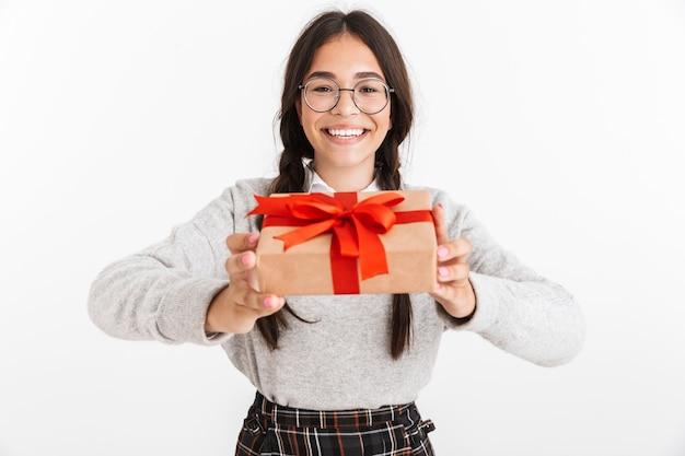 Zbliżenie portreta zachwyconej nastoletniej dziewczyny w okularach, uśmiechniętej, trzymając pudełko z czerwoną kokardą na białym tle nad białą ścianą