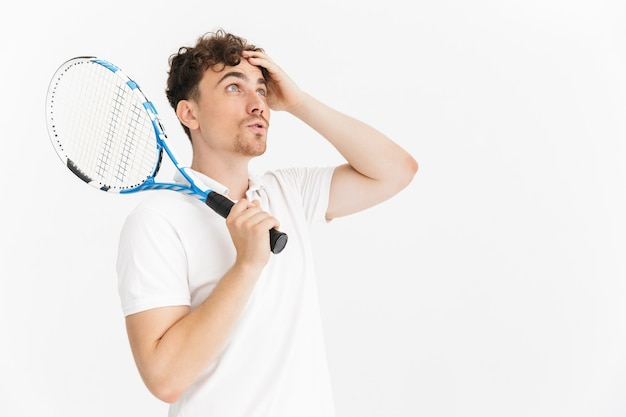 Zbliżenie portreta zdziwionego mężczyzny w koszulce patrzącego na bok i trzymającego rakietę podczas gry w tenisa na białym tle nad białą ścianą