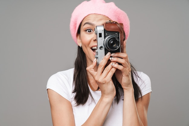 Zbliżenie portreta zdziwionej młodej kobiety turystycznej w berecie, zastanawiającej się i portretującej na retro starodawnym aparacie izolowanym na szarej ścianie