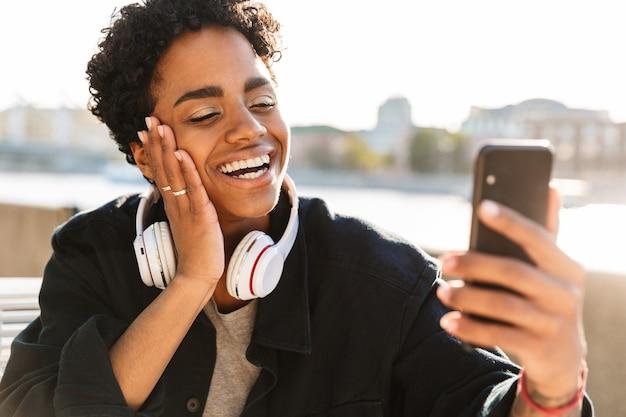Zbliżenie portretowe przyjaznej kobiety ze słuchawkami nawiązującej połączenie wideo na smartfonie siedząc na ławce w pobliżu brzegu rzeki