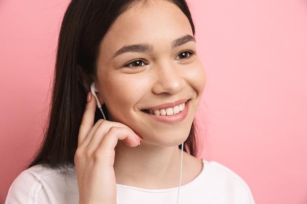 Zbliżenie portretu optymistycznej ładnej dziewczyny noszącej słuchawki uśmiechniętej podczas słuchania muzyki odizolowanej na różowej ścianie