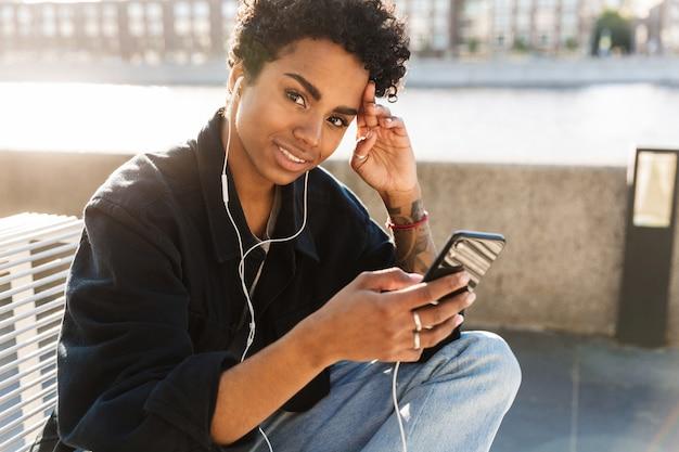Zbliżenie portretu pięknej kobiety słuchającej muzyki na telefonie komórkowym ze słuchawkami, siedząc na ławce w pobliżu brzegu rzeki