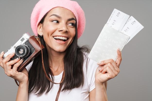 Zbliżenie portretu uwodzicielskiej ładnej turystycznej kobiety w berecie, uśmiechającej się, trzymając aparat retro i bilety podróżne na białym tle nad szarą ścianą