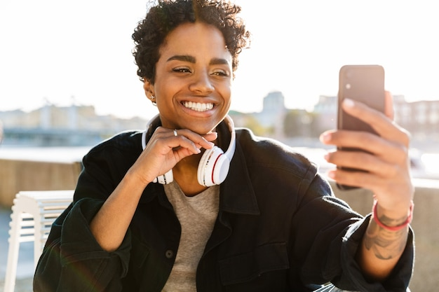 Zbliżenie portretu wesołej kobiety ze słuchawkami nawiązującej połączenie wideo na smartfonie, siedząc na ławce w pobliżu brzegu rzeki