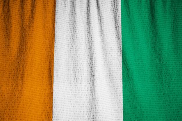 Zbliżenie potargane cote d ivoire flaga, wybrzeże kości słoniowej flaga dmuchanie w wiatr