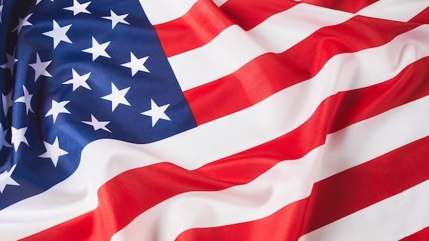 Zbliżenie potargane flagi amerykańskiej satynowa tekstura zakrzywiona flaga usa banner i koncepcja wolności