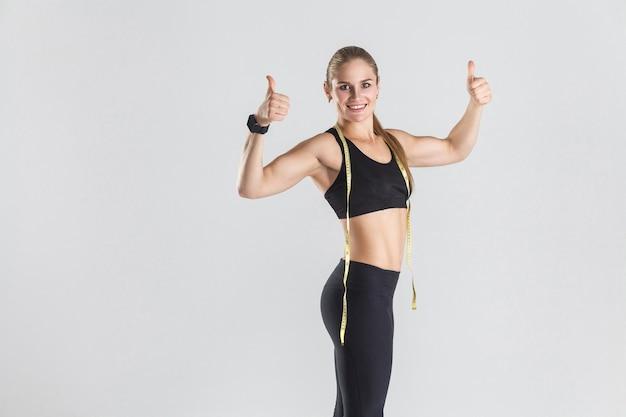 Zbliżenie potężna muskularna dziewczyna pokazująca kciuki do góry w aparacie