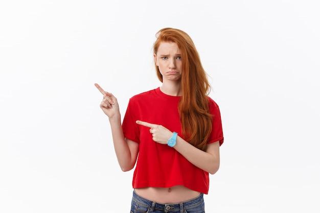 Zbliżenie poważna surowa młoda kobieta jest ubranym czerwoną koszula patrzeje stresującą się i wskazuje up z palcem odizolowywającym nad bielem