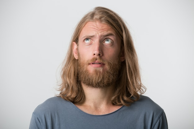 Zbliżenie poważnego atrakcyjnego młodzieńca z brodą i blond długimi włosami nosi szarą koszulkę wygląda zamyślony i zamyślony na białym tle nad białą ścianą