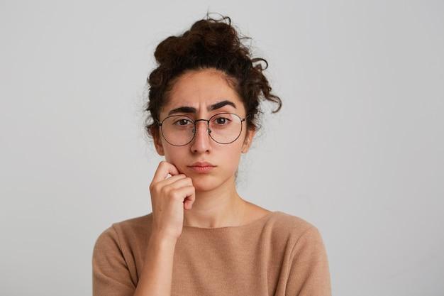 Zbliżenie poważnej zamyślonej blondynki młoda kobieta nosi koszulę w kropki, trzyma ręce złożone, wygląda zamyślony i myśli na białym tle nad białą ścianą
