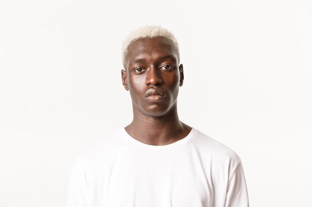 Zbliżenie: poważny przystojny afroamerykanin blond stylowy facet, patrząc na aparat zdeterminowany i spokojny